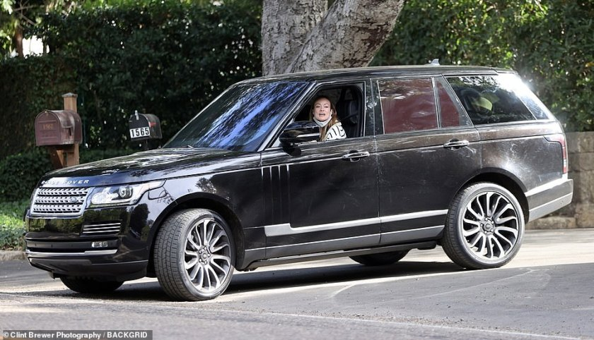 Good times: Olivia looked in good spirits as she drove her new love's car while wearing a face mask