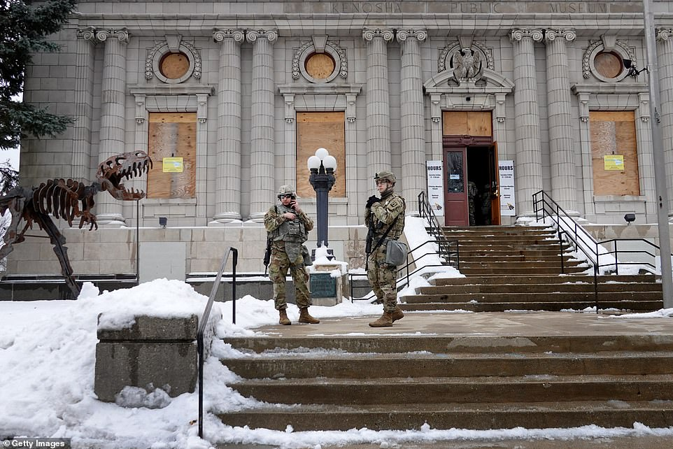 National Guard troops standing guard near the Kenosha County Courthouse hours before the charges announcement on Tuesday above