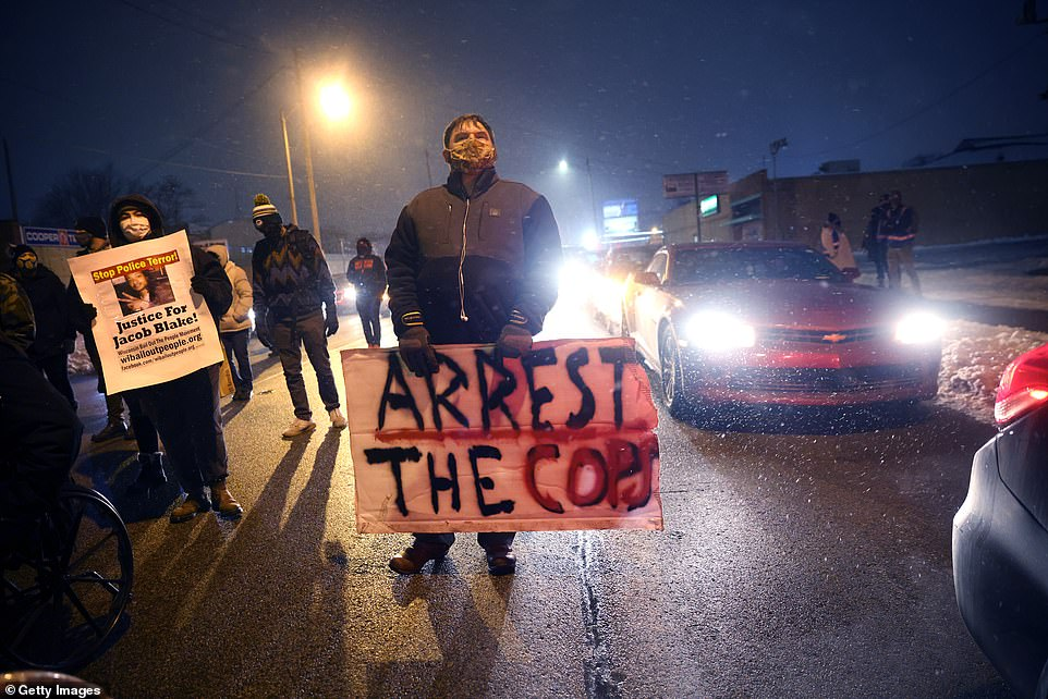 Activists show support for Jacob Blake during a vigil near the Kenosha County Courthouse on January 4