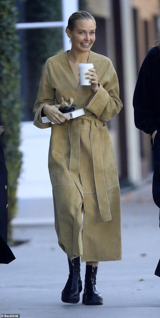 Trendsetter: Lara looked effortlessly stylish in a tan duster coat and chunky leather boots