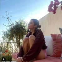Ashley Benson puts her pert backside on display while lounging outside in tiny pink workout shorts