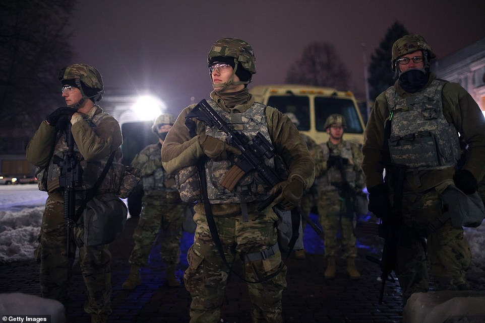 : National Guard troops stand watch as demonstrators protest outside of the Kenosha County Courthouse