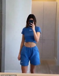 Kendall Jenner flaunts her toned tummy in a blue crop top and sweat shorts at home in Los Angeles
