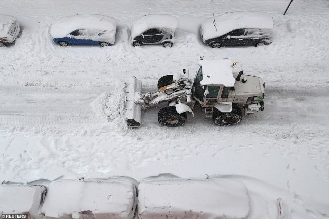 A bulldozer works its way along a road in Madrid, pushing snow out of the way in an attempt to clear the road