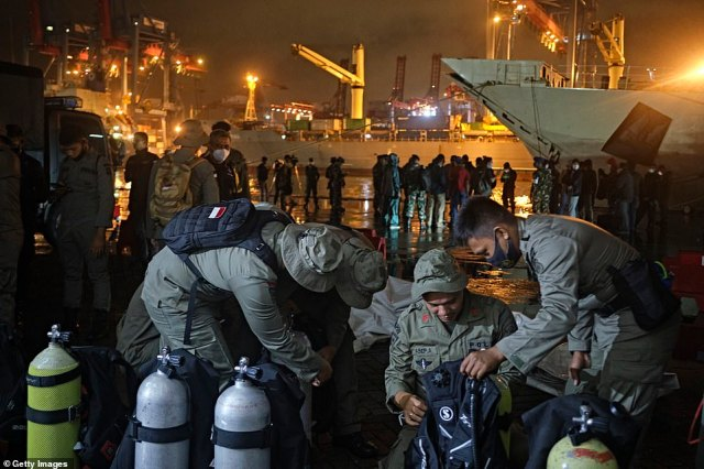 Indonesian Police divers check their gear before embarking on the search and rescue operation for the missing plane