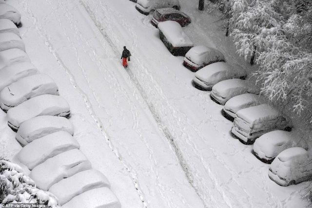 Barely visible: This aerial shot captures the extent of the snowfall in Madrid, with two lines of cars on either side of a road almost completely invisible beneath the blanket of snow