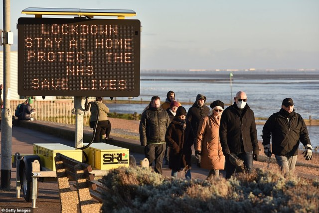 "People walk past a digital public safety notice saying ""Lockdown, StayAt Home, Protect The NHS, Save Lives"" along the seafront at Westcliff beach on January 9, in Southend"