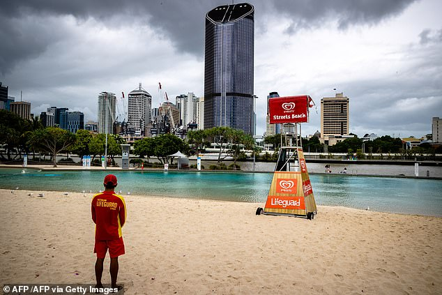 Greater Brisbane will remain in lockdown until 6pm Monday. Pictured is a lifeguard at a deserted South Bank Beach on Saturday