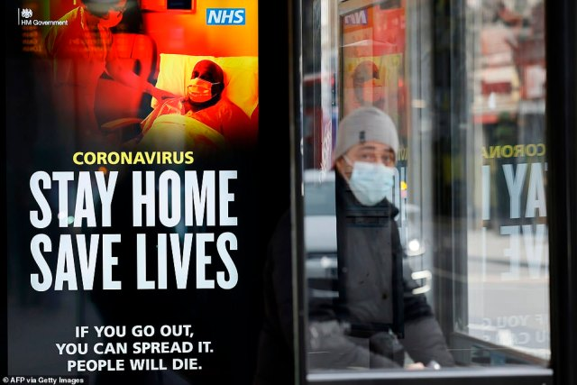"""A commuter wears a facemask as he sits in a bus shelter with signage promoting """"Stay Home, Save Lives"""" in central London"""
