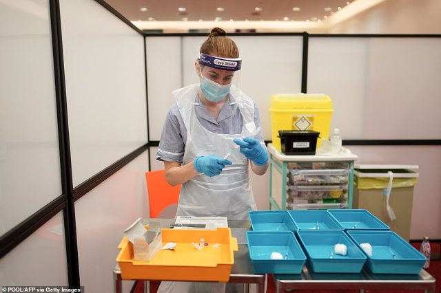 A healthcare professional prepares a dose of Pfizer/BioNTech Covid-19 vaccine for health and social care workers at the Life Science Centre at the International Centre for Life in Newcastle