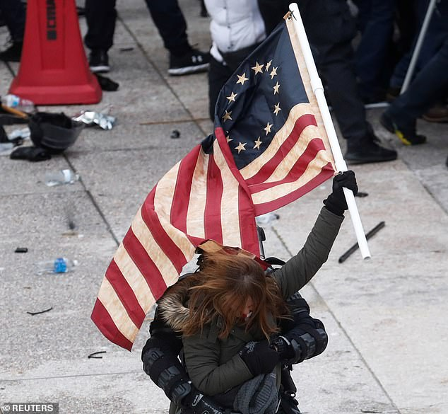 Pictured, a Trump supporter holding a Betsey Ross flag is detained by a police officer at the U.S. Capitol on Wednesday. The flag is not strictly an extremist symbol but has been used by groups as a signal of an idea of more traditional America, which they believe is whiter and male