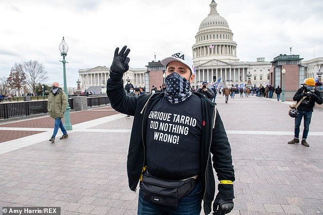 A Proud Boy displays a white power symbol on Wednesday in D.C. as he wears a t-shirt that protests the innocence of the group's leader Enrique Tarros who was recently arrested