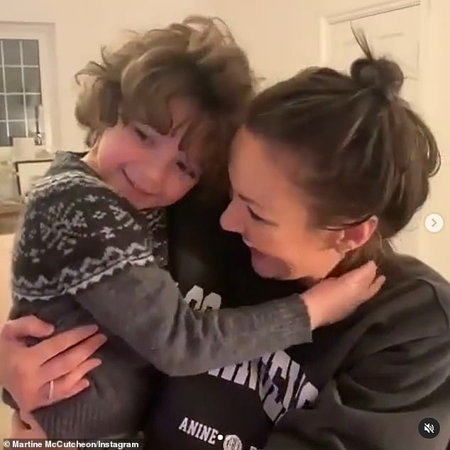 Sweet: In the clip uploaded to social media, she was seen holding her five-year-old child while they watched the ITV programme and Martine chanted at her onscreen character: 'Take it off'