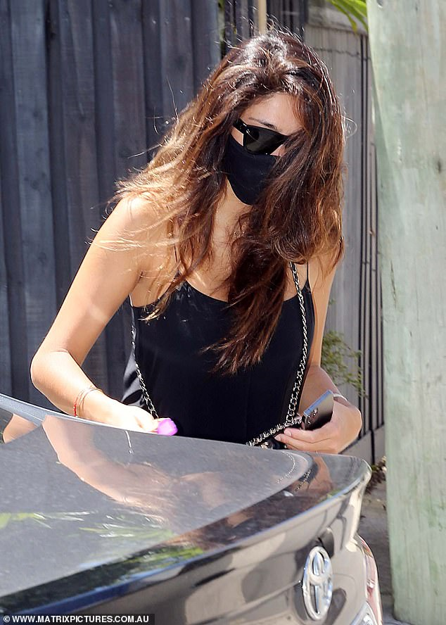 Back in black:The 37-year-old covered up her face in a black, satin face mask, and a pair of sunglasses.Her mask matched her slinky slip dress, under which she appeared to go braless