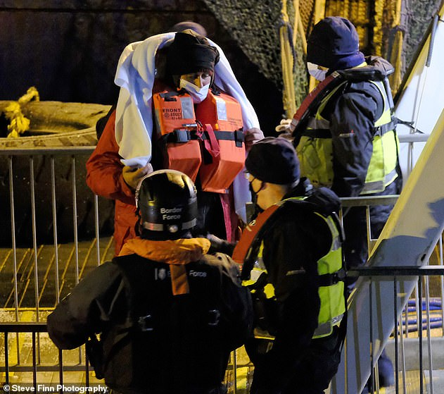 A migrant wears a life jacket as they are brought ashore by officials in Dover, Kent, on Sunday morning