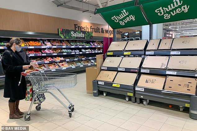 Gaps appearing on supermarket fruit and veg shelves are thought to be due to Brexit red tape at ports and staff shortages at food producers due to Covid. Pictured: Empty fruit and veg shelves in Sainsbury's in Cambridge on Jan 6