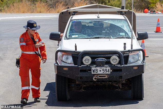 SES crews check restricted access permits issued to residents at a check point about 120km north of Perth
