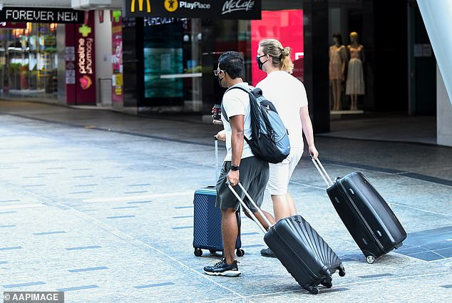 People carrying luggage wear face masks as they make their way through Brisbane CBD amid lockdowns on January 11
