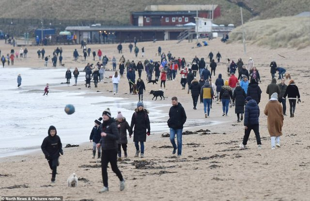 Crowds of people were seen flocking to beaches and town centres today despite Boris Johnson's pleas for families to stay at home as coronavirus hospital deaths hit 563 - the highest Sunday toll in eight months. Pictured: Visitors on Tynemouth Longsands beach