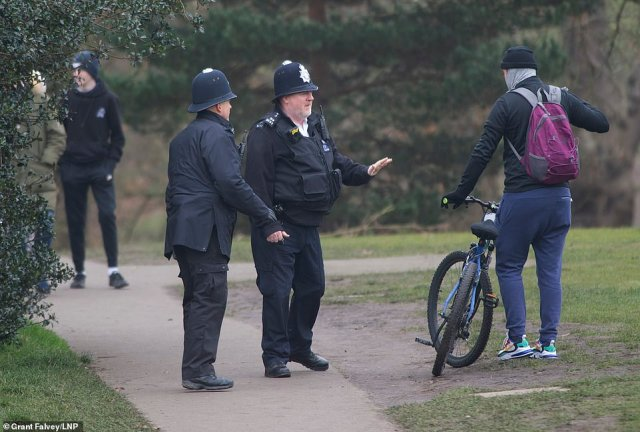 Police officers talk to a cyclist in Greenwich on Sunday