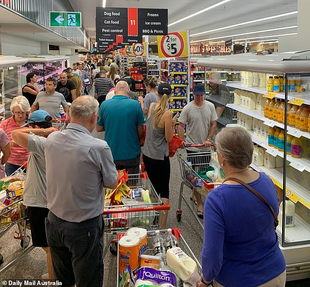 Shoppers swamped supermarkets in Brisbane (pictured Coles, New Farm on Friday) to stock up after being told the city would go into a three-day lockdown for coronavirus