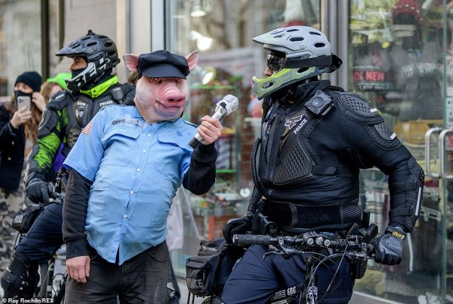 Face to face: A protester wearing a mock police uniform and a pig's head holds a microphone towards an NYPD officer on a bicycle during Sunday's Antifa protest in Manhattan