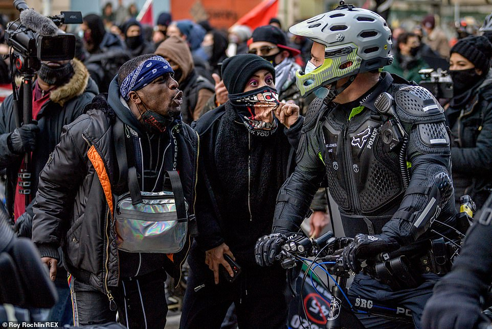 Eye to eye: One protester lowered his mask to harangue a police officer during Sunday's protest, which comes amid fears of further political violence ahead of the inauguration of Joe Biden and Kamala Harris on January 20