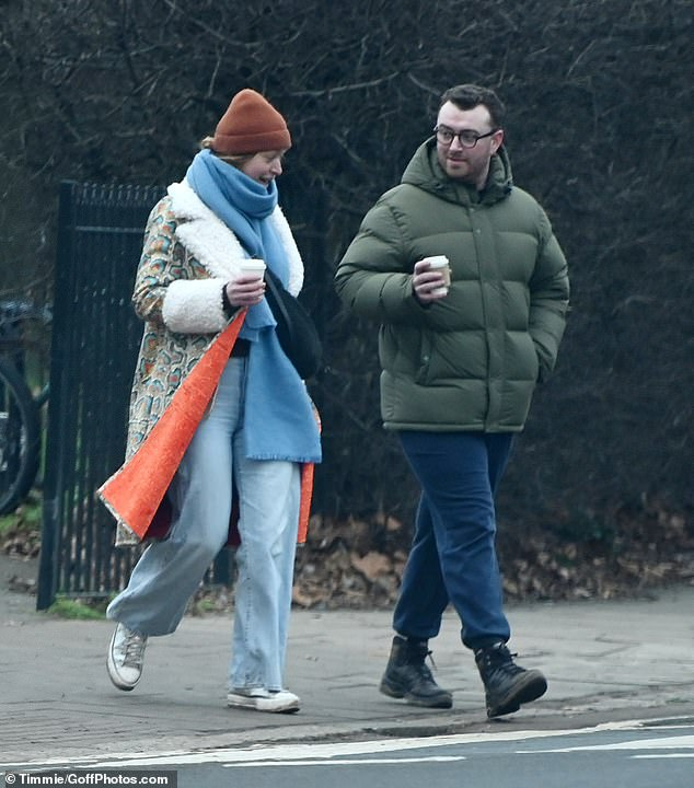 Out and about: Sam Smith bundled up against the cold in a green padded jacket as they enjoyed a socially distanced walk with a pal on Sunday