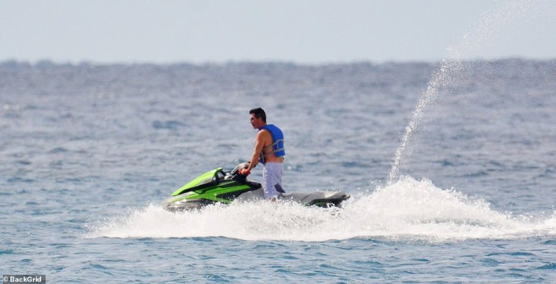 Thrills: Simon was spotted indulging in one of his favourite holiday activities, speeding around the shore on his jetski