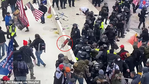 Moments later, another rioter comes out of nowhere and throws the fire extinguisher over the heads of the police in the crowd.