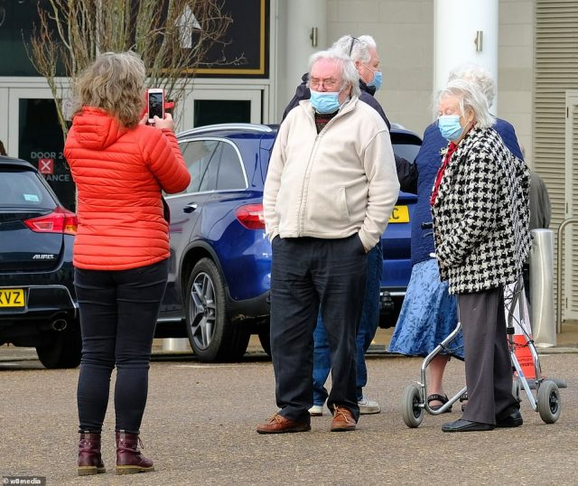 An elderly couple pose for a photo outside the Epsom racecourse as they enter for their lifesaving jab