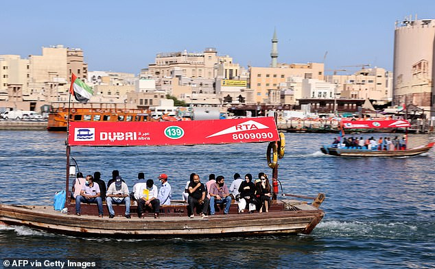 People ride a boat at the Ras El-Khor wildlife sanctuary near the old quarter of Dubai