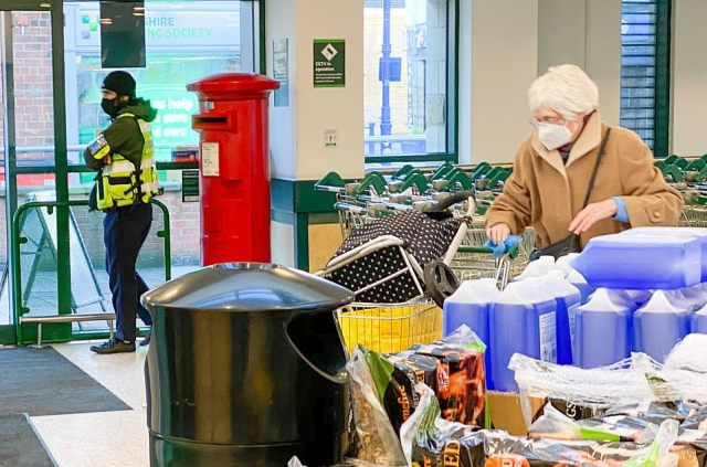 A security guard on duty at the entrance to a Morrisons in Leeds, where most customers were following the face mask guidance