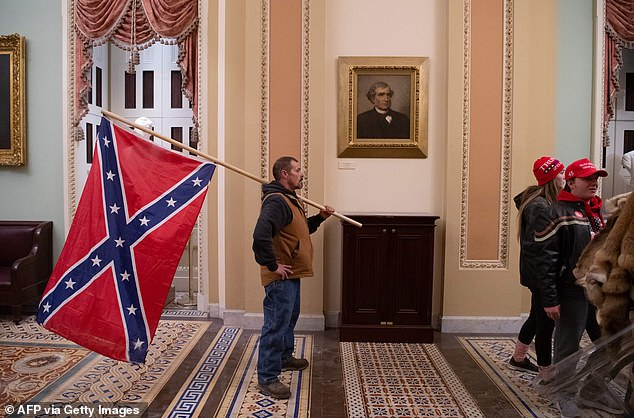 A supporter of US President Donald Trump holds a Confederate flag outside the Senate Chamber during the raid of the Capitol