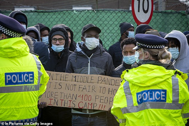Asylum seekers currently held inside Napier Barracks staged a protest outside the entrance to the barracks with banners and signs to demonstrate about the poor living conditions