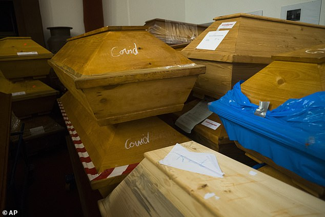 Caskets labelled with the word 'Covid' are stacked with others in the memorial hall in Meissen
