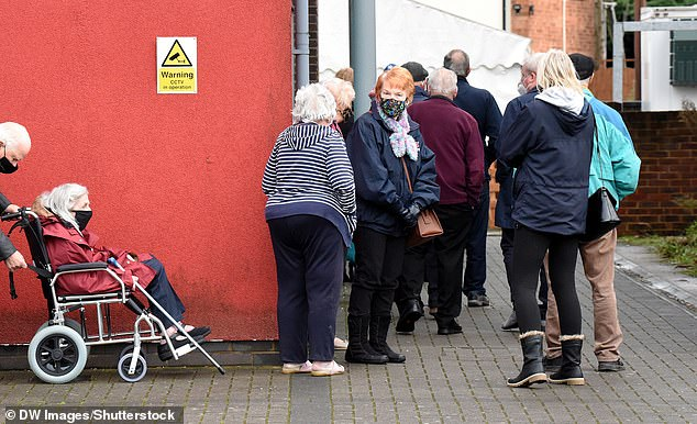 Dozens of elderly people queue outside Hornchurch library in the London Borough of Havering for their Covid-19 vaccine