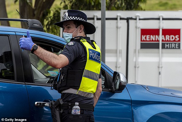 Victoria has gone one week without a locally-acquired coronavirus case after the New South Wales outbreak jumped the border. Pictured: A Victoria Police officer gestures to colleagues at a border checkpoint