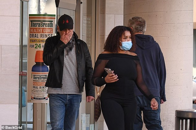 Swift exit: Bruce, 65, is seen covering his face with his hand as he left the pharmacy