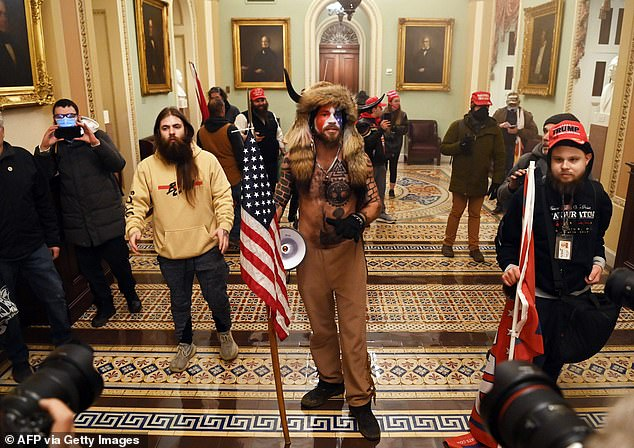 Chansley is one of the MAGA rioters who turned himself in to the FBI for his part in storming the Capitol building last Wednesday. Chansley above wearing a fur headdress with horns and his chest bare during the Capitol siege Wednesday