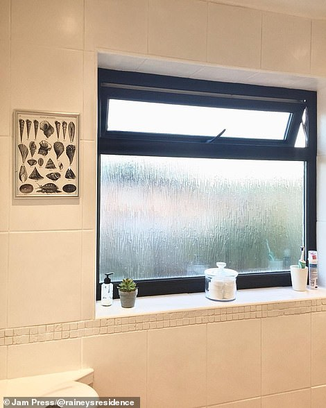 The bathroom is pictured after the work was completed - and boasts new white tiles and tasteful finishing touches