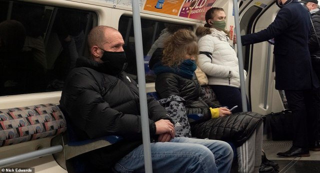 Commuters wear face coverings while travelling on the Jubilee line through the capital this morning