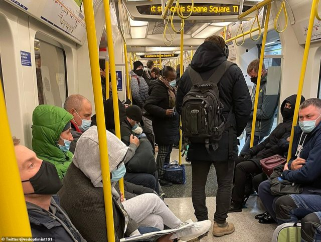 A busy Circle or District line train on the London Underground this morning while stopped at Victoria station