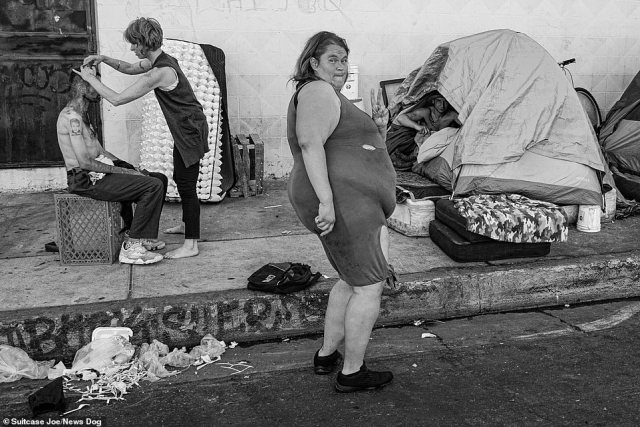 A series of photographs taken on Los Angeles' 'Skid Row' - where the city's largest community of homeless people are based - have been released by street photographer Suitcase Joe in a new book. Pictured: A group of homeless people on Skid Row, one of whom is seen inside a tent on the sidewalk, another receives a hair cut, as a woman walks down the street