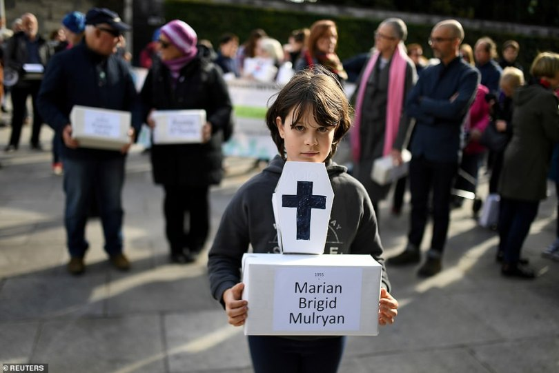 A child holds a funeral box at a procession for infants whose bodies were found in a septic tank in 2014 - a discovery which led to Tuesday's damning report