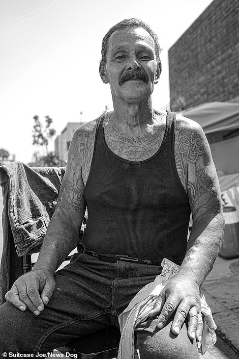 A resident of Skid Row gives a wry smile as he sits for his portrait.