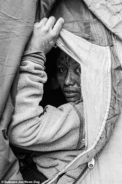 Jenny looks out from her tent that is located in Skid Row