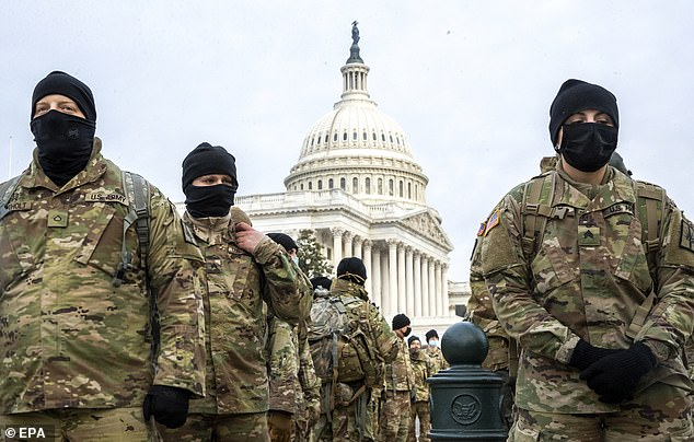 Members of the New York National Guard form up on the East Front of the Capitol asat least 10,000 troops are deployed in Washington D.C.