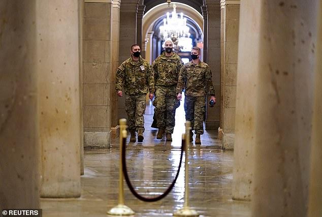 U.S. National Guard members walk among the columns of the crypt beneath the U.S. Capitol rotunda