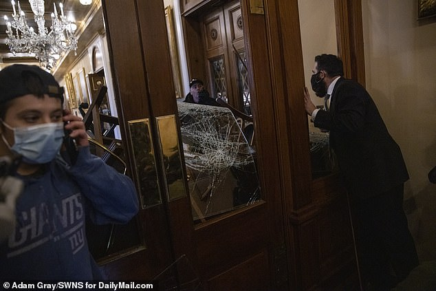 Baranyi is pictured left on the phone as Capitol police tried to clear the builiding Wednesday